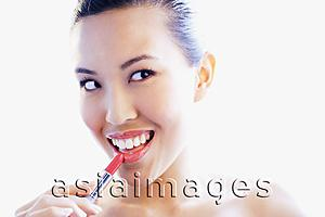 Asia Images Group - Woman applying lipstick, looking away, smiling