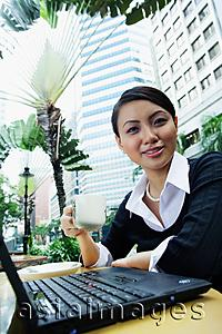 Asia Images Group - Business woman with laptop, holding coffee cup, smiling at camera