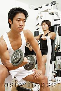 Asia Images Group - Young men working out in gym, looking away