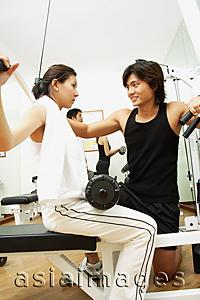 Asia Images Group - Couple working out in gym, woman lifting weights, man helping her