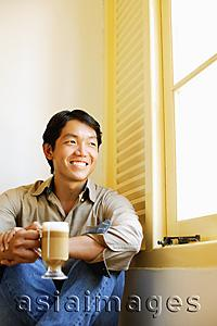 Asia Images Group - Man sitting next to window holding mug of coffee