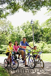 Asia Images Group - Family with two children, on bicycles, portrait