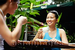 Asia Images Group - Two women at outdoor cafe, drinking coffee