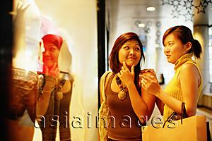 Asia Images Group - Young women looking at window display, talking