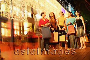 Asia Images Group - Young women standing side by side, in a row, carrying shopping bags