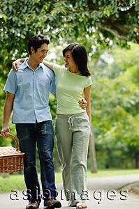 Asia Images Group - Couple walking in park, man carrying picnic basket