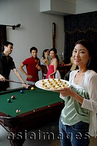 Asia Images Group - Woman with plate of appetizers, smiling at camera, people in the background