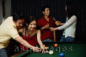 Asia Images Group - Man teaching woman to play snooker, people in the background