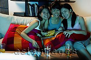 Asia Images Group - Three young women in living room, sitting on sofa, smiling at camera