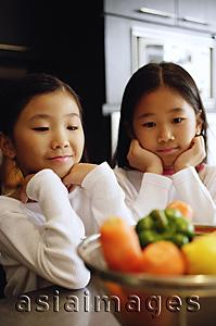 Asia Images Group - Two girls looking at a bowl of vegetables