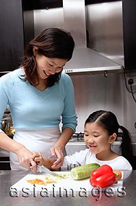 Asia Images Group - Mother cutting vegetables, daughter helping her