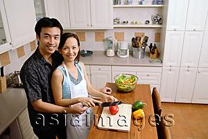 Asia Images Group - Couple in kitchen, woman cutting vegetables, smiling up at camera