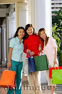 Asia Images Group - Three women with shopping bags, smiling at camera