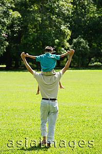 Asia Images Group - Father carrying son on shoulders, walking in field
