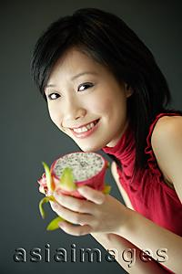 Asia Images Group - Woman holding cut dragon fruit, smiling at camera