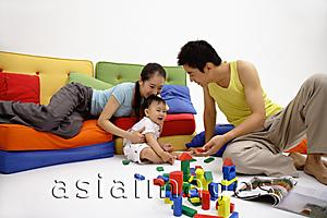 Asia Images Group - Family with one child, sitting in living room, playing with wooden toy blocks