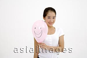 Asia Images Group - Woman holding pink balloon with smiley face drawn on it