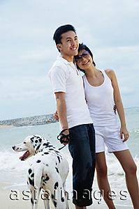 Asia Images Group - Couple standing on beach with Dalmatian