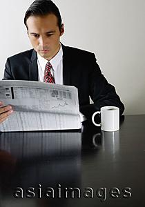 Asia Images Group - Businessman sitting at table reading newspaper, mug on table next to him