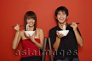 Asia Images Group - Couple sitting against red wall, holding bowl of noodles, smiling at camera