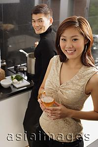 Asia Images Group - Couple in kitchen, man cooking at stove, woman holding wine glass