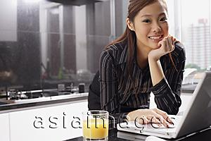 Asia Images Group - Female executive in kitchen with laptop, hand on chin, smiling at camera