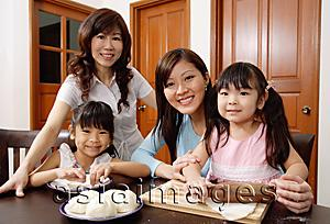 Asia Images Group - Three generations of females, in kitchen, smiling at camera