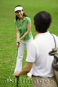 Asia Images Group - Couple on golf course, woman preparing to swing, smiling at man in foreground