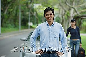 Asia Images Group - Man with hands on hips, standing in front of car, woman in the background with luggage