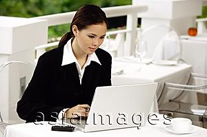 Asia Images Group - Businesswoman sitting in restaurant, using laptop