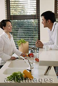 Asia Images Group - Couple in kitchen, woman chopping vegetables, man leaning on counter looking at her