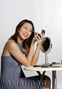 Asia Images Group - Woman looking at compact mirror, applying eyeshadow