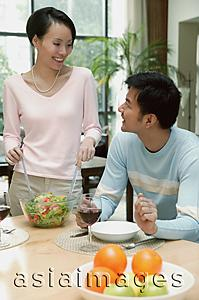 Asia Images Group - Man sitting at dining table, woman standing next to him tossing a salad