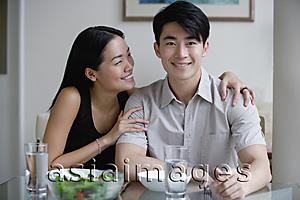 Asia Images Group - Couple at home, sitting by dining table, man looking at camera