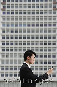 Asia Images Group - Businessman with mobile phone, side view