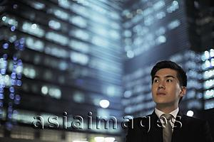 Asia Images Group - Man wearing a suit standing in front of lit buildings at night