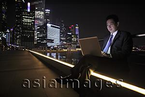 Asia Images Group - Mature man working on a laptop at night, lit buildings as background