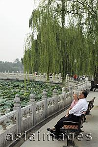 Asia Images Group - Older couple sitting on park bench looking at view