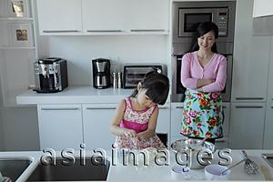 Asia Images Group - Mother watching her daughter cook in the kitchen
