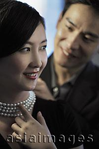Asia Images Group - Young man putting a pearl necklace on a woman