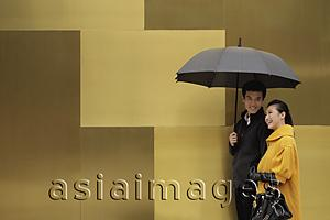 Asia Images Group - Young couple walking on street holding an umbrella