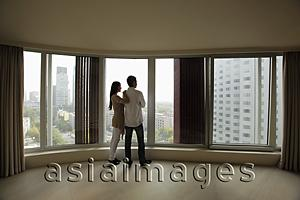Asia Images Group - Rear view of young couple looking out large windows of condo