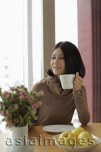 Asia Images Group - Young woman holding coffee looking out the window
