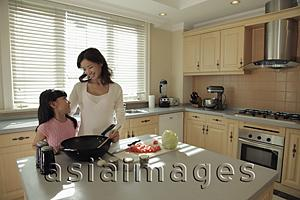 Asia Images Group - Mother and daughter cooking food together in the kitchen