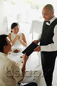AsiaPix - Couple in restaurant, man handing menu back to waiter