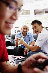 AsiaPix - Two men toasting with drinks, looking at camera, another man using mobile phone in the foreground