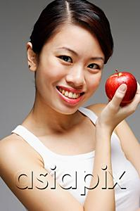 AsiaPix - Woman holding apple, looking at camera