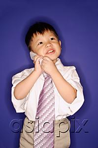 AsiaPix - Boy wearing oversized tie, using mobile phone