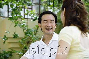 AsiaPix - Mature couple sitting, facing each other, smiling