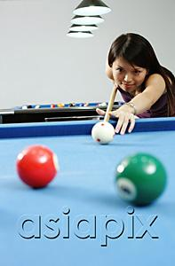AsiaPix - Woman holding pool cue, aiming at ball